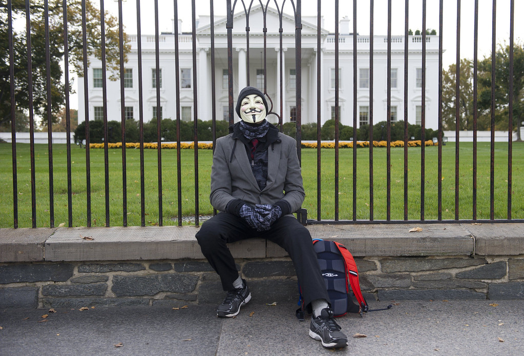 . A demonstrator sits while supporters of the group Anonymous, march in a protest against corrupt governments and corporations in front of the White House in Washington, DC, November 5, 2013, as part of a Million Mask March of similar rallies around the world on Guy Fawkes Day. AFP PHOTO / Saul LOEB/AFP/Getty Images