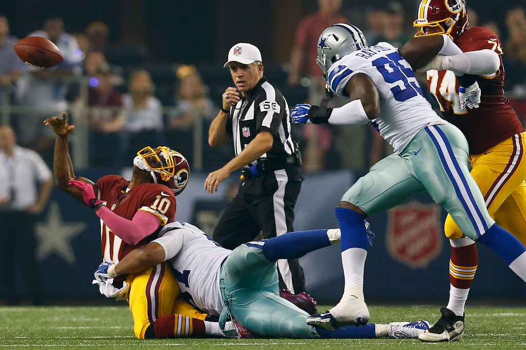 . ARLINGTON, TX - OCTOBER 13:   Robert Griffin III #10 of the Washington Redskins is sacked by Jason Hatcher #97 of the Dallas Cowboys for a loss in the second quarter on October 13, 2013 in Arlington, Texas.  (Photo by Tom Pennington/Getty Images)