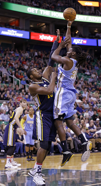 . Denver Nuggets\' Kenneth Faried (35) shoots as Utah Jazz\'s Derrick Favors, right, defends in the first quarter during an NBA basketball game Monday, Nov. 11, 2013, in Salt Lake City.  (AP Photo/Rick Bowmer)
