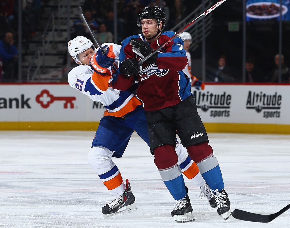 . DENVER, CO - JANUARY 10:  John Mitchell #7 of the Colorado Avalanche puts a hit on Kyle Okposo #21 of the New York Islanders at Pepsi Center on January 10, 2014 in Denver, Colorado.  (Photo by Doug Pensinger/Getty Images)
