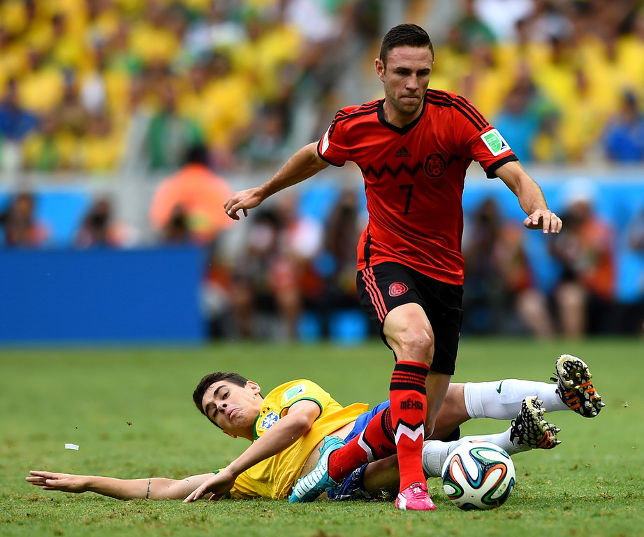. Oscar of Brazil tackles Miguel Layun of Mexico during the 2014 FIFA World Cup Brazil Group A match between Brazil and Mexico at Castelao on June 17, 2014 in Fortaleza, Brazil.  (Photo by Buda Mendes/Getty Images)