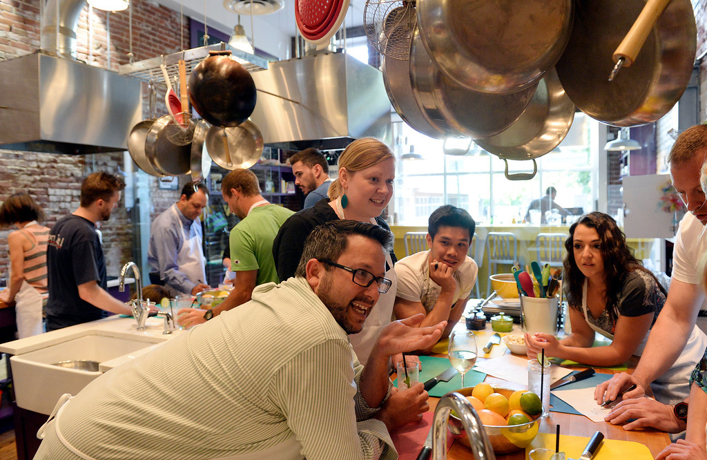 . DENVER, CO - JUNE 6: The Stir Cooking School at 3215 Zuni Street in Denver, hosted an Iron Chef styled cooking event  on Friday, June 6, 2014.  The evening pitted three tables competing against one another. Contestants in the foreground left to right:  Tony Thielen, Carrie Pearse,  Ben Koh,  and Rachel Vento,  strategize for their meal.  (Denver Post Photo by Cyrus McCrimmon)