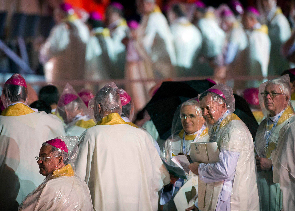 . Bishops wearing plastic rain hoods attend the World Youth Day inaugural Mass on Copacabana beach, in Rio de Janeiro, Brazil, Tuesday, July 23, 2013. A cold rain Tuesday night didn\'t stop upward of 500,000 faithful from gathering on Rio\'s Copacabana beach to mark the event. (AP Photo/Domenico Stinellis)