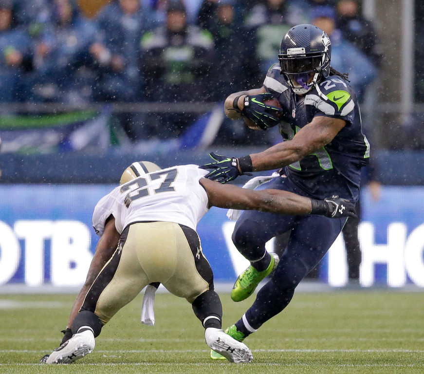 . Seattle Seahawks running back Marshawn Lynch, right, runs against New Orleans Saints free safety Malcolm Jenkins during the first half of an NFC divisional playoff NFL football game in Seattle, Saturday, Jan. 11, 2014. (AP Photo/Elaine Thompson)