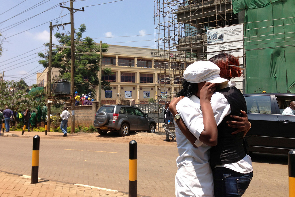. Two women hug outside an upscale shopping mall, seen background left , in Nairobi, Kenya Saturday Sept. 21 2013, after shooting erupted when armed men attempted to rob a store. Bursts of gunfire were heard from outside the mall Saturday, where cars were left abandoned. Witnesses say a half dozen grenades also went off along with lobbies of  gunfire that started at midday. Police say they are engaging the attackers. (AP Photo/ Jason Straziuso)
