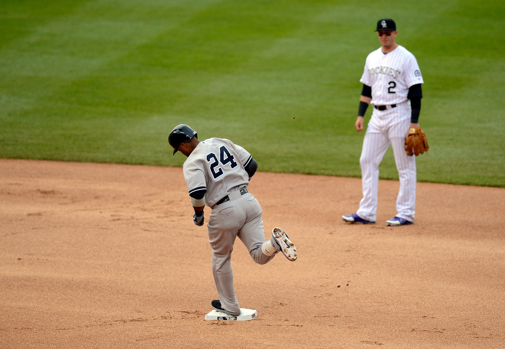 . Troy Tulowitzki (2) of the Colorado Rockies looks on as Robinson Cano (24) of the New York Yankees rounds second base after his  home run in the fifth inning off of Adam Ottavino (0) of the Colorado Rockies May 9, 2013 at Coors Field. (Photo By John Leyba/The Denver Post)
