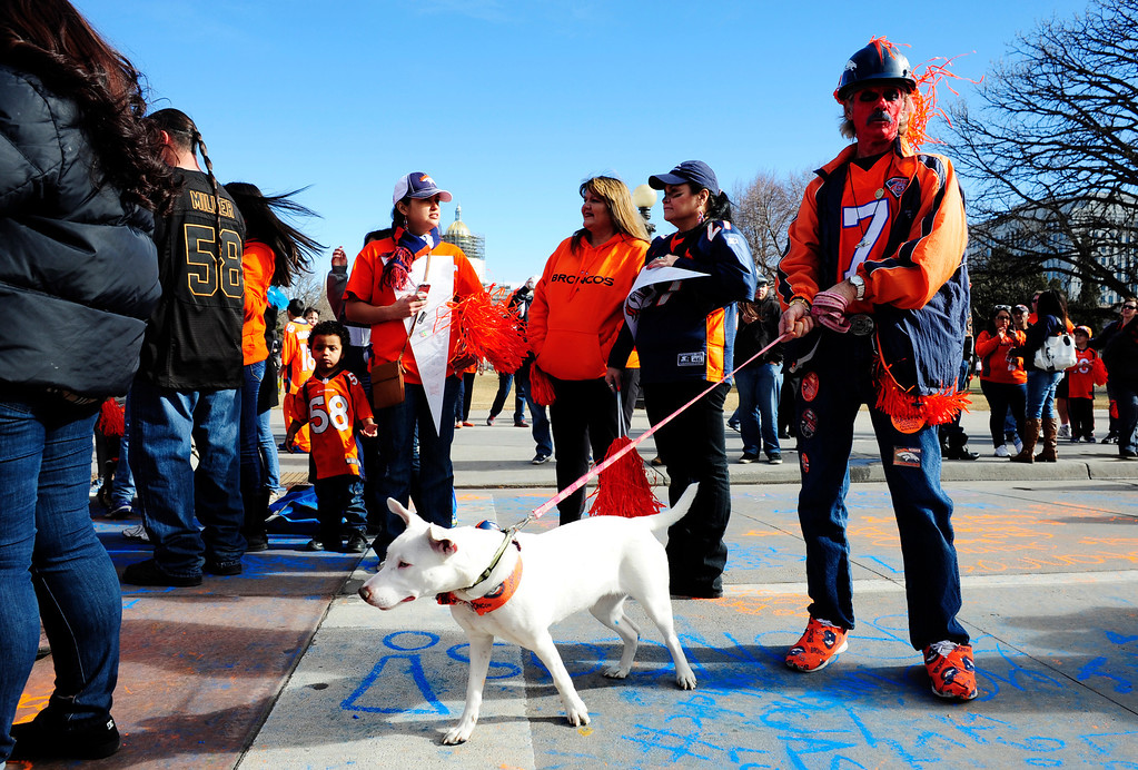 . Tim Hyatt (right), holds his dog McKenzie, during a rally to send off the Denver Broncos, at the City and County Building in Denver, Colorado, Sunday, January 26, 2014. The noon rally brought out scores of supporters and included an appearance by Governor John Hickenlooper and Denver Mayor Michael Hancock.  (Photo By Brenden Neville / Special to The Denver Post)