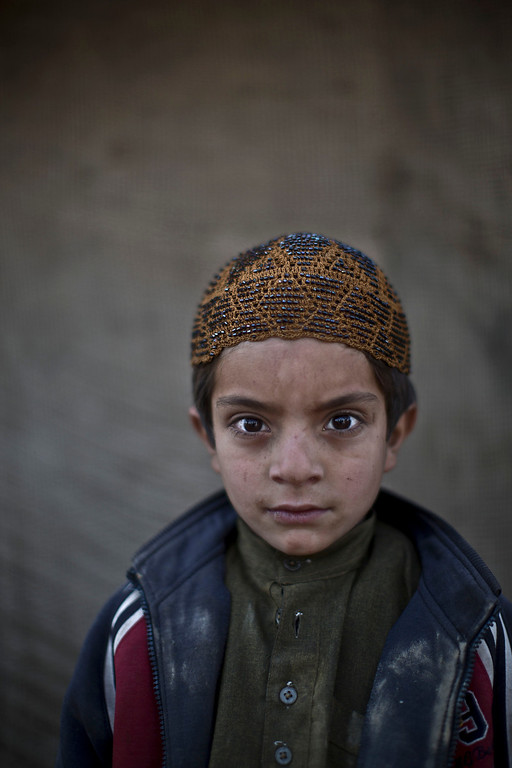 . In this Monday, Jan. 27, 2014 photo, Afghan refugee boy, Allam Ahmad, 6, poses for a picture, while playing with other children in a slum on the outskirts of Islamabad, Pakistan. For more than three decades, Pakistan has been home to one of the world�s largest refugee communities: hundreds of thousands of Afghans who have fled the repeated wars and fighting their country has undergone. Since the 2002 U.S.-led invasion of Afghanistan, some 3.8 million Afghans have returned to their home country, according to the U.N.�s refugee agency. (AP Photo/Muhammed Muheisen)