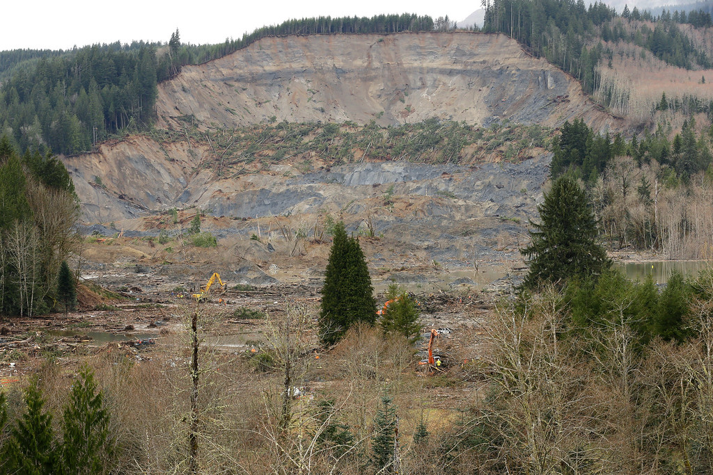 . The scene of the massive deadly mudslide that hit the community of Oso, Wash. on Saturday, March 22, 2014 is shown Sunday, March 30, 2014 with heavy equipment working to clear trees and debris, near Darrington, Wash., as the search for victims continues. (AP Photo/Ted S. Warren)