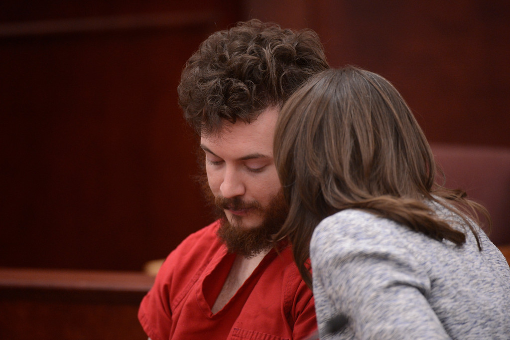 . Aurora theater shooting suspect James Holmes confers with Defense attorney Tamara Brady in the courtroom during his arraignment Tuesday March 12, 2013.  (Photo By RJ Sangosti/The Denver Post)