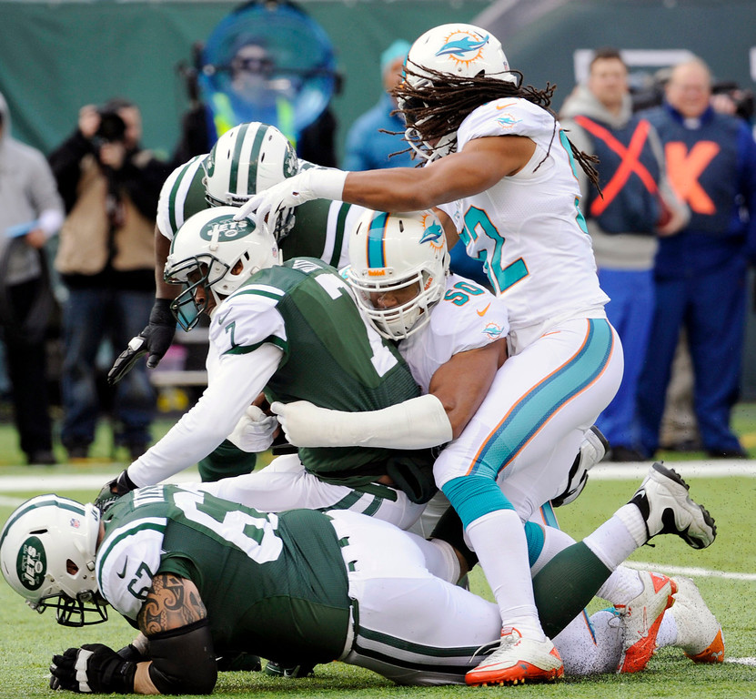 . New York Jets quarterback Geno Smith, center left, is sacked by Miami Dolphins defensive end Olivier Vernon, center right, during the first half of an NFL football game Sunday, Dec. 1, 2013, in East Rutherford, N.J. (AP Photo/Bill Kostroun)