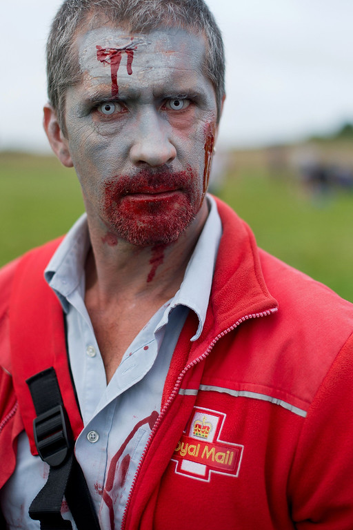 ". A volunteer zombie Royal Mail postman prepares to take part in one of Britain\'s biggest horror events, the ""Zombie Evacuation Race\"" at Carver Barracks near Saffron Walden, England, on October 5, 2013. The race sees thousands of participants attempt to complete a gruelling 5 kilometre cross-country run, while evading \""zombies\"", intent on snatching the three life-line strips hanging from every runner\'s waist.  Those who manage to get through with any strips remaining are named as survivors while those without take home an \""infected\"" badge.  LEON NEAL/AFP/Getty Images"