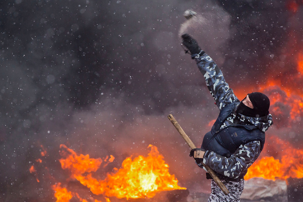 . A protester throws a Molotov cocktail during clashes with police in central Kiev, Ukraine, Wednesday, Jan. 22, 2014. Two people whose dead bodies were found Wednesday near the site of clashes with police have been shot with live ammunition, prosecutors said Wednesday, an announcement that could further fuel violence that spilled on the streets of the Ukrainian capital after two months of largely peaceful protests.(AP Photo/Evgeny Feldman)