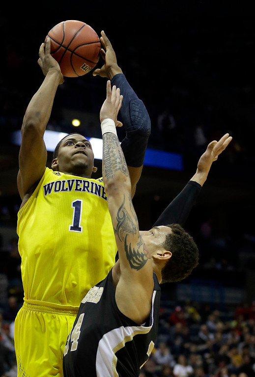 . Michigan forward Glenn Robinson III (1) goes up for a shot over Wofford forward Lee Skinner (34) during the first half of a second round NCAA college basketball tournament game Thursday, March 20, 2014, in Milwaukee. (AP Photo/Morry Gash)