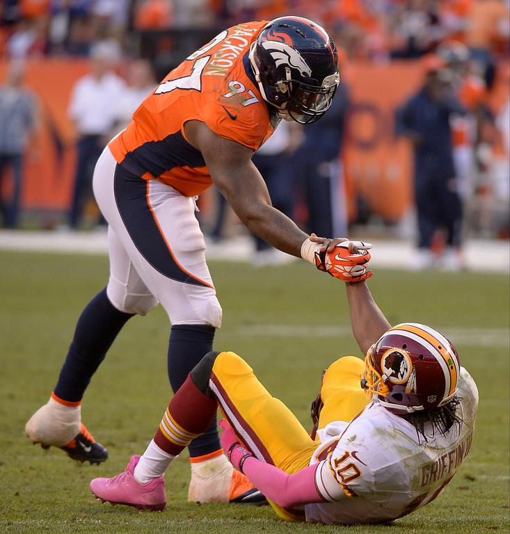 . Denver Broncos defensive end Malik Jackson (97) helps Washington Redskins quarterback Robert Griffin III (10) up in the fourth quarter.  (Photo by John Leyba/The Denver Post)