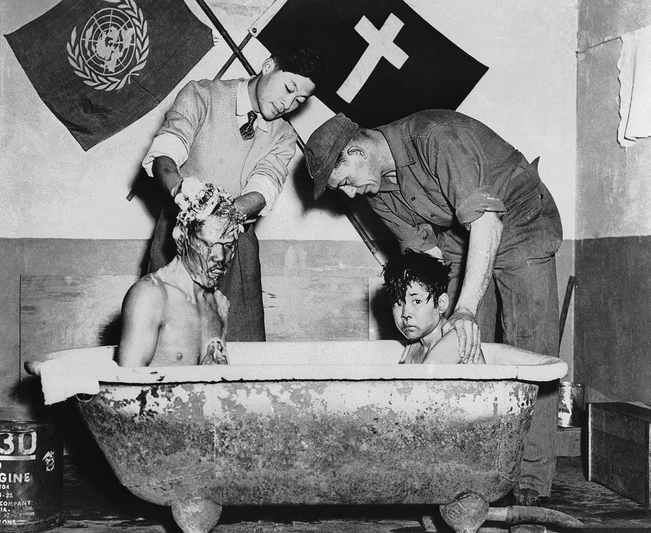 . Air Force Cpl. Joseph P. Lany (right) of 639 main St. Torrington, Conn., scrubs Coo Jany Soo, 14-year-old Korean war orphan, in Korea on March 26, 1952 as a Korean helper does likewise with Soo\'s older brother, Sun, who has been blind since birth. This is part of the program of the Fifth Air Force\'s 839th Engineer Aviation Battalion to alleviate some of the suffering and misery caused by the Korean War. Korean orphans are rounded up from impromptu homes and are given medical treatment, warm clothing and a good meal. The battalion then arranges for their transportation to an orphanage sponsored by the U.N. for unfortunate waifs. Soo\'s parents were killed by the Reds more than a year ago as they attempted to cross the lines and gain refuge with UN forces. (AP Photo)