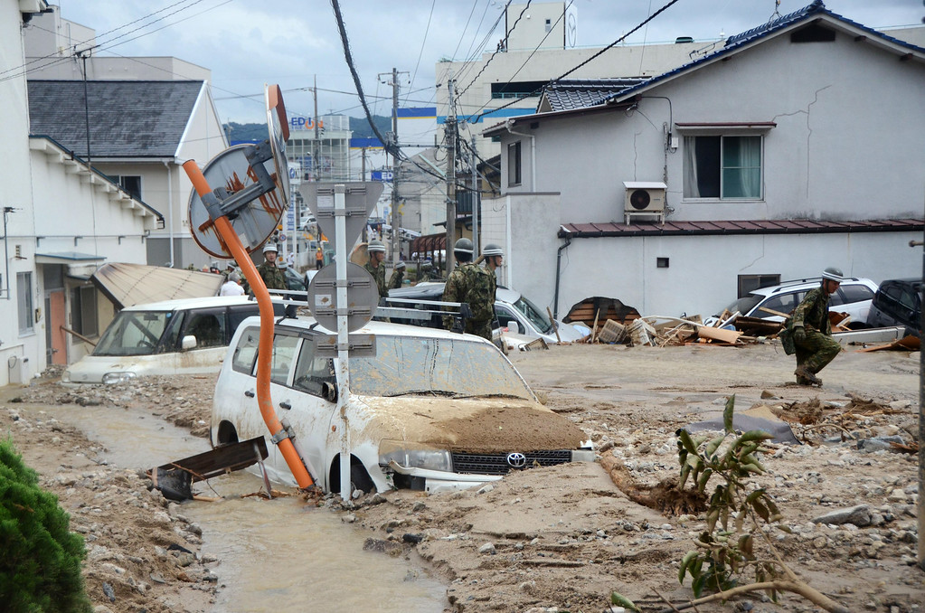 . A rescuer walks through knee-deep mud after a massive landslide swept through residential areas in Hiroshima, western Japan, Wednesday, Aug. 20, 2014. (AP Photo/Kyodo News)
