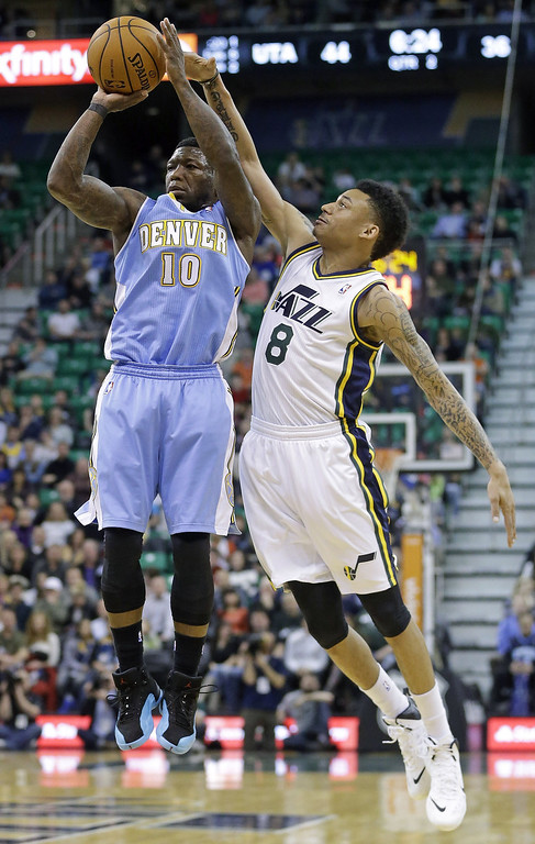 . Denver Nuggets\' Nate Robinson (10) shoots as Utah Jazz\'s Diante Garrett (8) defends in the second quarter during an NBA basketball game, Monday, Jan. 13, 2014, in Salt Lake City. (AP Photo/Rick Bowmer)
