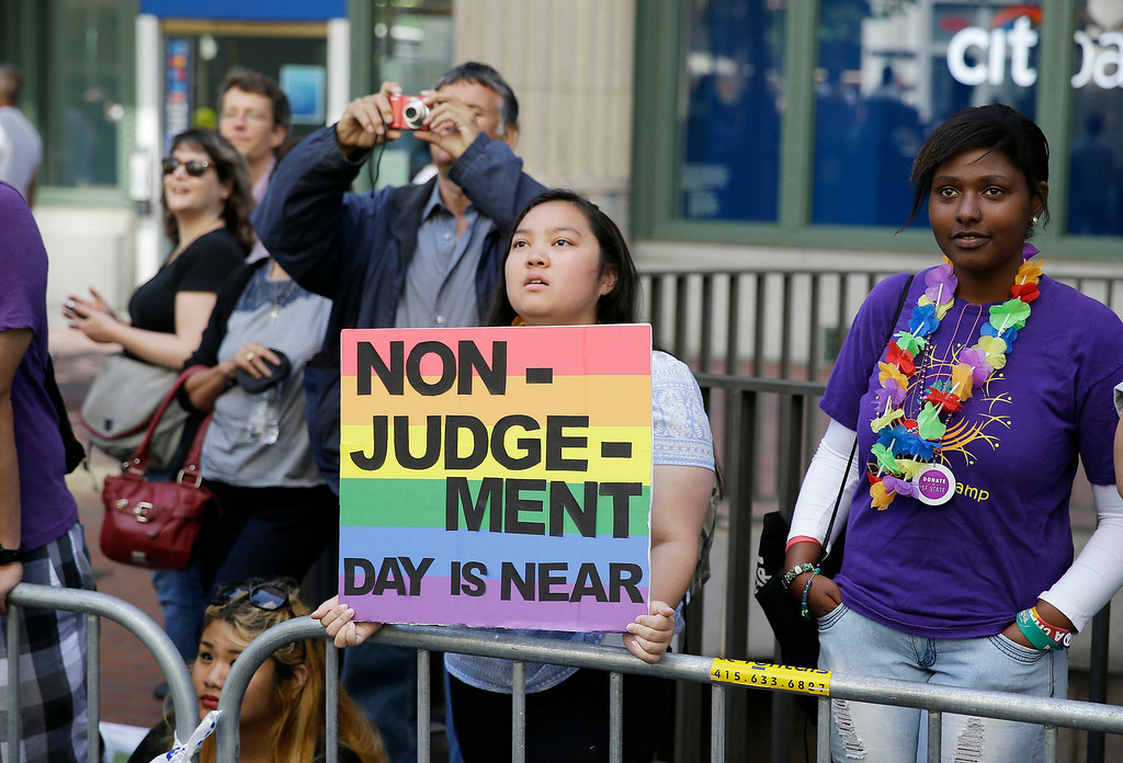 . Eliza Galimba, 16, holds up a sign while watching the 44th annual San Francisco Gay Pride parade Sunday, June 29, 2014, in San Francisco. The lesbian, gay, bisexual, and transgender celebration and parade is one of the largest LGBT gatherings in the nation. (AP Photo/Eric Risberg)