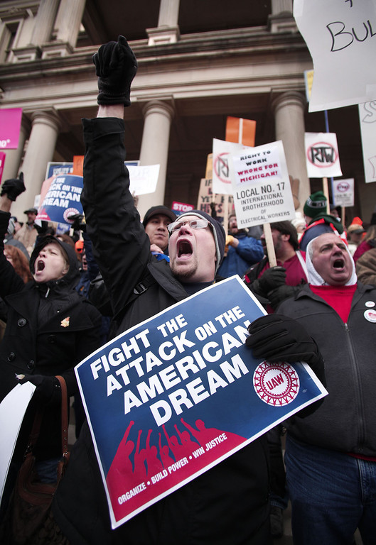 . Craig Cable, of Newport, Michigan, a member of United Auto Workers Union Local 3000, and union members from around the country, rally at the Michigan State Capitol to protest a vote on Right-to-Work legislation December 11, 2012 in Lansing, Michigan. Republicans control the Michigan House of Representatives, and Michigan Gov. Rick Snyder has said he will sign the bill if it is passed. The new law would make requiring financial support of a union as a condition of employment illegal. (Photo by Bill Pugliano/Getty Images)