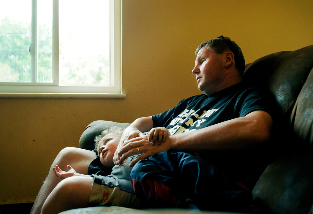 . Brent sits with one of his 2-yr-old twins after a day of work.  Photo by Jamie Cotten, Special to The Denver Post