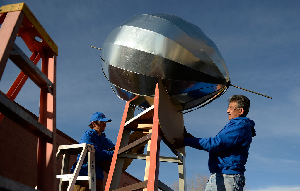 . John Darling, left, Carlos Tovar, both employees at Frontier Roofing System in east Denver, work on making a 14-foot Vince Lombardi Trophy, January, 26 2014. The owner of the roofing company, Bob Schmitz, is a huge Denver Broncos fan and wants the trophy to drive around downtown Denver, and to bring to his families Super Bowl party. (Photo by RJ Sangosti/The Denver Post)