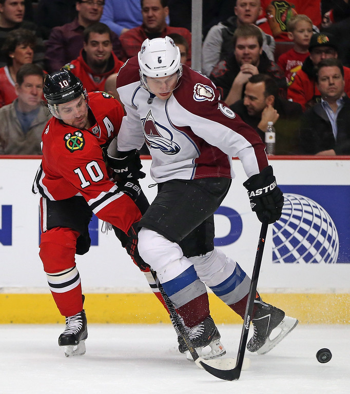 . Patrick Sharp #10 of the Chicago Blackhawks knocks the puck away from Erik Johnson #6 of the Colorado Avalanche at the United Center on January 14, 2014  in Chicago, Illinois. (Photo by Jonathan Daniel/Getty Images)