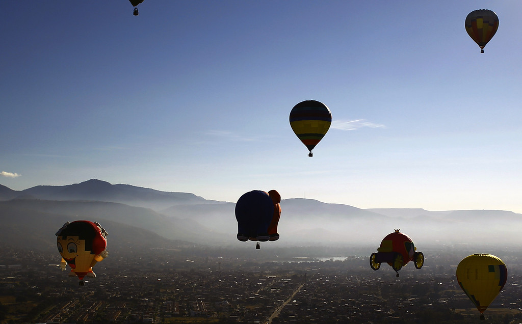 . Hot air balloons fly over the Metropolitan Park in Leon City, Guanajuato State, Mexico, during the International Balloon Festival on November  15, 2013. About 200 balloonists from 16 different countries take part in the festival.   AFP PHOTO/Hector GUERRERO/AFP/Getty Images