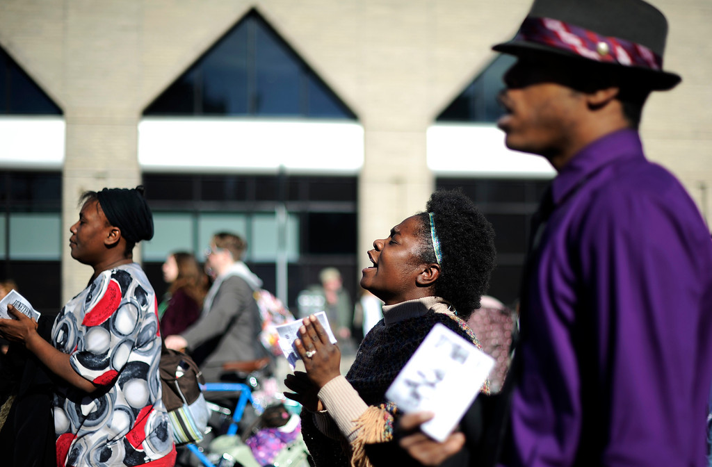 . Larea Edwards, center, and Yves Rhone II , right, sing with a group from the Rapture Missionary Baptist Church as  they walk in the  Martin Luther King Jr. Marade  as it winds along E. Colfax Ave. on it\'s way downtown.  The marade, march/parade,  started at the MLK statue in the City Park  on Monday, January 21, 2013.   (Photo By Cyrus McCrimmon / The Denver Post)