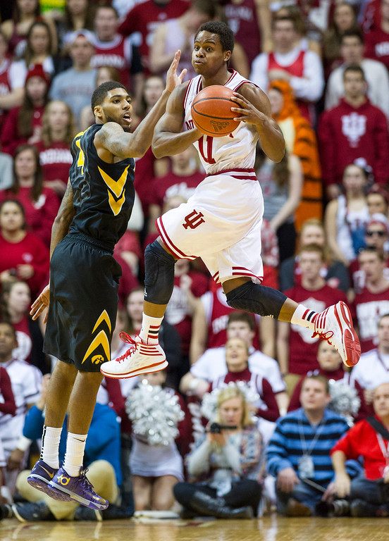 . Indiana\'s Yogi Ferrell (11) changes course and looks for a teammate to pass to as Iowa\'s Roy Devyn Marble (4) goes up to defend against his efforts in the first half of an NCAA college basketball game on Thursday, Feb. 27, 2014, in Bloomington, Ind. (AP Photo/Doug McSchooler)