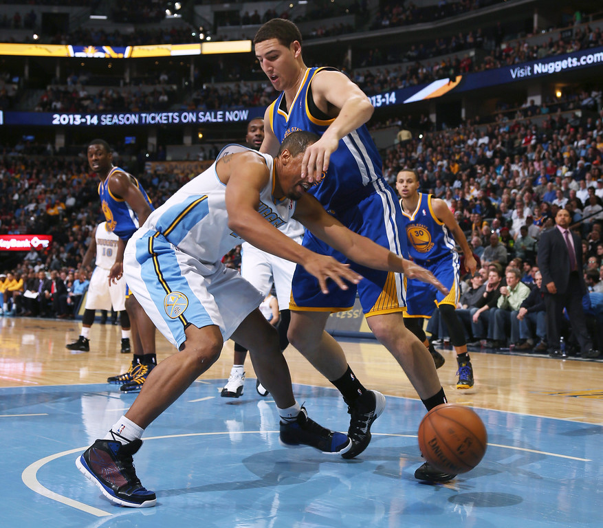 . Denver Nuggets guard Andre Miller, left, loses control of the ball as he drives the lane and into Golden State Warriors guard Klay Thompson during the fourth quarter of the Warriors\' 89-81 victory in an NBA basketball game in Denver on Monday, Dec. 23, 2013. (AP Photo/David Zalubowski)