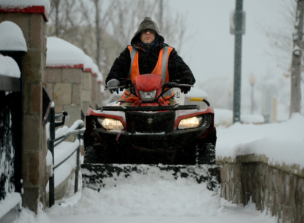 . LITTLETON, CO. - MARCH 23:  Ron Loera, of Grounds Services Co. uses an ATV to clear the walk at the RTD station in downtown Littleton, CO March 23, 2013. The Saturday forecast calls for snow accumulation of 9 to 12 inches with highs in the lower to mid 20s. (Photo By Craig F. Walker/The Denver Post)