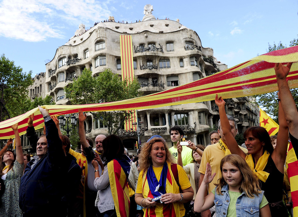 . Catalans link arms in a bid to create a 400-kilometre (250-mile) human chain, part of a campaign for independence from Spain during Catalonia National Day, or Diada, in front of the Pedrera in Barcelona, on September 11, 2013. Independence-seeking Catalans  marshalled their forces today to make a human link they say will stretch across 86 cities, towns and villages along the coast of the northeastern region on the Mediterranean, passing landmarks such as the Sagrada Familia basilica in Barcelona and the city\'s Camp Nou football stadium. JOSEP LAGO/AFP/Getty Images