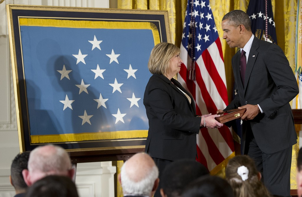 . US President Barack Obama presents Laurie Wegner with a Medal of Honor for her late uncle Army Private First Class Leonard Kravitz during a ceremony in the East Room of the White House in Washington on March 18, 2014. Obama awarded the Medal of Honor to 24 veterans, 3 of whom are still living, who fought in World War II, the Korean War and the Vietnam War, most of whom were previously denied the prestigious honor due to their Hispanic, black or Jewish backgrounds. The ceremony results from a Pentagon review of Jewish and Hispanic war records ordered by Congress in 2002.    AFP PHOTO / Saul LOEB/AFP/Getty Images