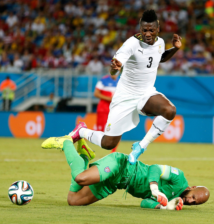 . Ghana\'s Asamoah Gyan (3) leaps over United States\' goalkeeper Tim Howard during the group G World Cup soccer match between Ghana and the United States at the Arena das Dunas in Natal, Brazil, Monday, June 16, 2014. (AP Photo/Julio Cortez)
