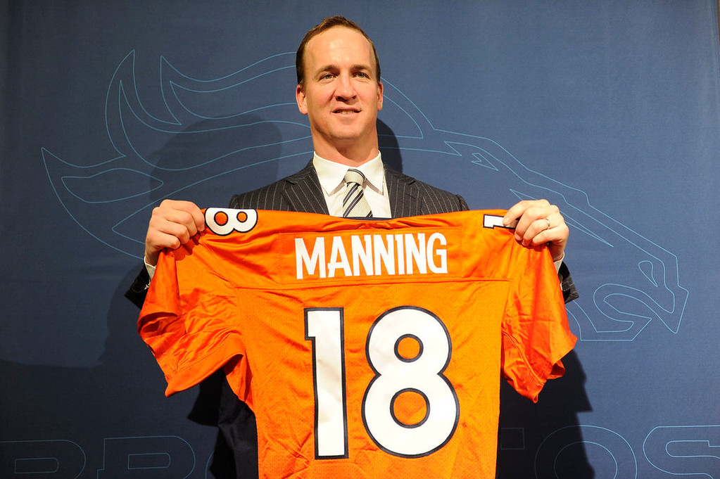 . Peyton Manning holds up his new Denver Broncos jersey during the Denver Broncos press conference announcing the signing of Manning on March 20, 2012 at Dove Valley. Photo by John Leyba, The Denver Post