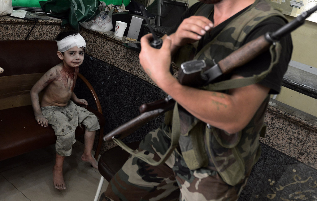 . A Syrian boy who was injured when a shell, released by regime forces, hit his house on August 24, 2012, waits to be treated at a hospital in Syria\'s northern city of Aleppo. Syrian forces blitzed areas in and around the Aleppo , activists said, as Western powers sought to tighten the screws on embattled President Bashar al-Assad. (ARIS MESSINIS/AFP/GettyImages)