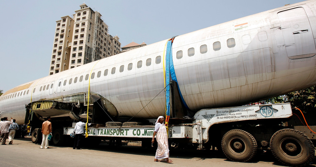 . People walk past the fuselage of a Boeing 737 parked on a road in Mumbai May 3, 2007. The trailer carrying the fuselage got stuck on a narrow road in Mumbai while being taken to New Delhi. REUTERS/Arko Datta