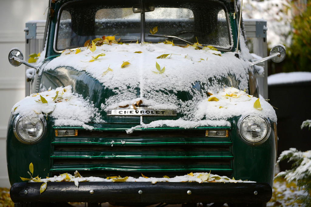 . An old Chevrolet truck covered in snow and fall leaves along Jackson St. near Yale Ave Friday morning, October 18, 2013.  (Photo By Andy Cross/The Denver Post)