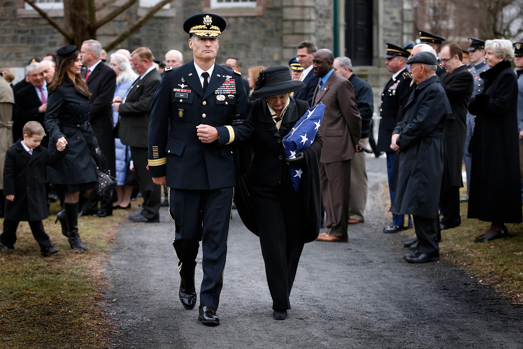 . Brenda Schwarzkopf, widow of the late U.S. Four Star General H. Norman Schwarzkopf, is escorted by Major General Kenneth Tovo at her late husband\'s graveside while holding an American flag at Schwarzkopf\'s burial service at the United States Military Academy at West Point, New York, February 28, 2013.  REUTERS/Mike Segar