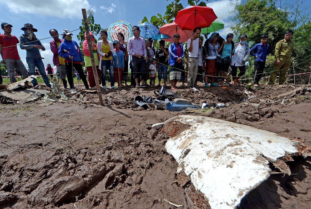 . Lao villagers look at pieces of a Lao Airlines plane after it crashed into the Mekong river near Pakse town, on October 17, 2013. Rescuers searched for bodies after a Lao Airlines plane believed to be carrying 49 people, around half of them foreigners, plunged into the Mekong River during stormy weather.  AFP PHOTO / PORNCHAI  KITTIWONGSAKUL/AFP/Getty Images