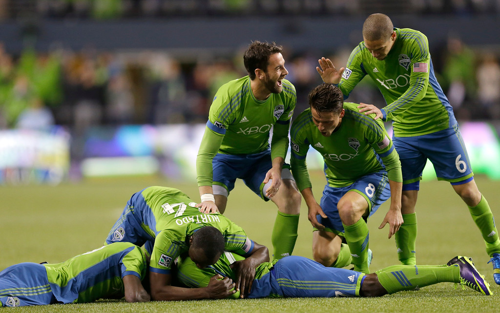 . Seattle Sounders\' Eddie Johnson lies on the ground and is mobbed by teammates, including Zach Scott, center, Marc Burch (8), and Osvaldo Alonso (6), after scoring a goal against the Colorado Rapids during stoppage time in a knockout-round match in the MLS Cup soccer playoffs, Wednesday, Oct. 30, 2013, in Seattle. The Sounders defeated the Rapids 2-0 and will advance to the Western Conference semifinals Saturday, Nov. 2, 2013, for a first of two aggregate match against the Portland Timbers. (AP Photo/Ted S. Warren)
