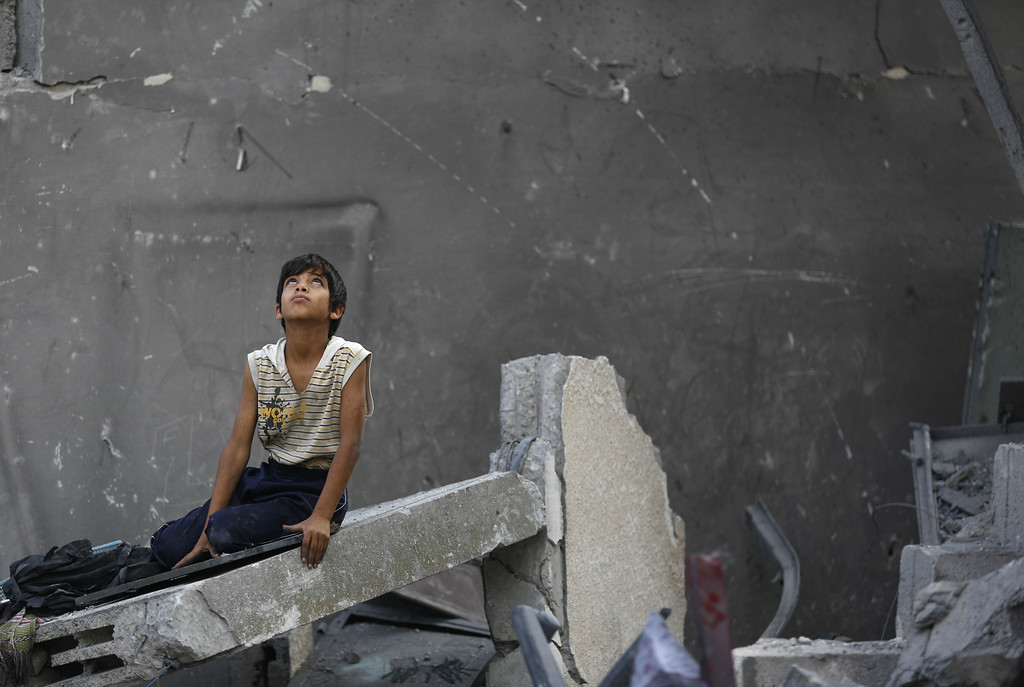 . A Palestinian boy sits on the rubble of a destroyed building following an Israeli air strike in the center of Gaza City on July 22, 2014. A series of Israeli air strikes early today killed at least seven people in Gaza, including five members of the same family, an emergency services spokesman said. The deaths hike the total Palestinian toll to 583 since the Israeli military launched Operation Protective Edge on July 8 in a bid to stamp out rocket fire from Gaza. AFP PHOTO / MOHAMMED ABED/AFP/Getty Images
