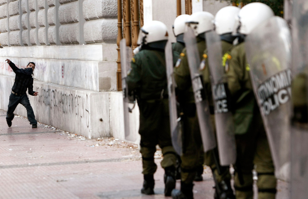 . A protester throws stones at riot police during clashes in central Athens December 7, 2009. Greek police fired teargas at hundreds of stone-throwing youths protests to mark the one-year anniversary of the police killing of a teenager. REUTERS/Yiorgos Karahalis