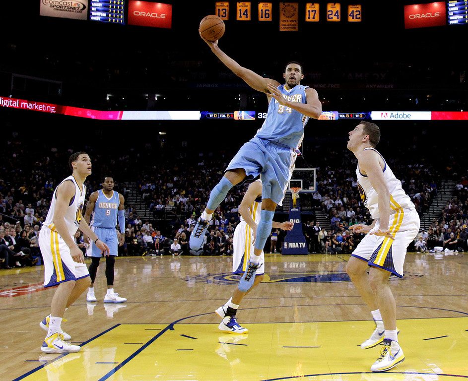 . Denver Nuggets\' JaVale McGee (34) shoots between Golden State Warriors\' David Lee, right, and Klay Thompson, left, during the first half of an NBA basketball game in Oakland, Calif., Thursday, Nov. 29, 2012. (AP Photo/Marcio Jose Sanchez)