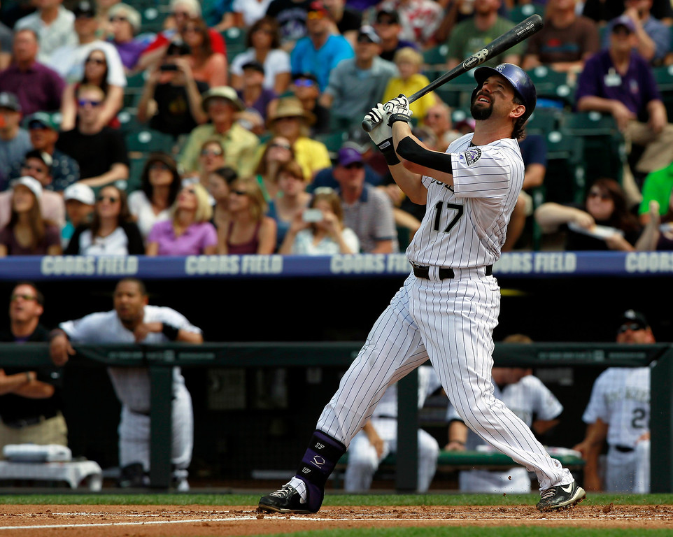 . Colorado Rockies\' Todd Helton follows the flight of his fly-out against the Cincinnati Reds to end the first inning of a baseball game in Denver, Sunday, Sept. 1, 2013. (AP Photo/David Zalubowski)