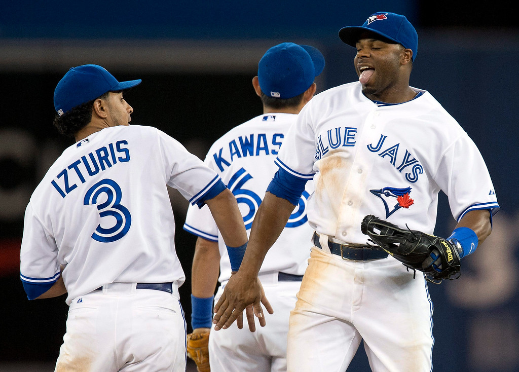 . Toronto Blue jays Maicer Izturis, left,  and Rajai Davis, right, celebrate after defeating the Colorado Rockies in a baseball game in Toronto on Monday June 17, 2013. Izturis had the game winning single to score Davis.   (AP Photo/The Canadian Press, Frank Gunn)