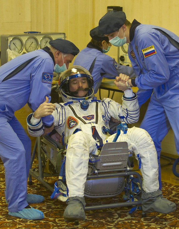 . Specialist help the International Space Station (ISS) crew member Canadian astronaut Chris Hadfield to get up after checking his space suit at the Baikonur cosmodrome Kazakhstan Wednesday, Dec. 19, 2012.  (AP Photo/ Shamil Zhumatov, pool)