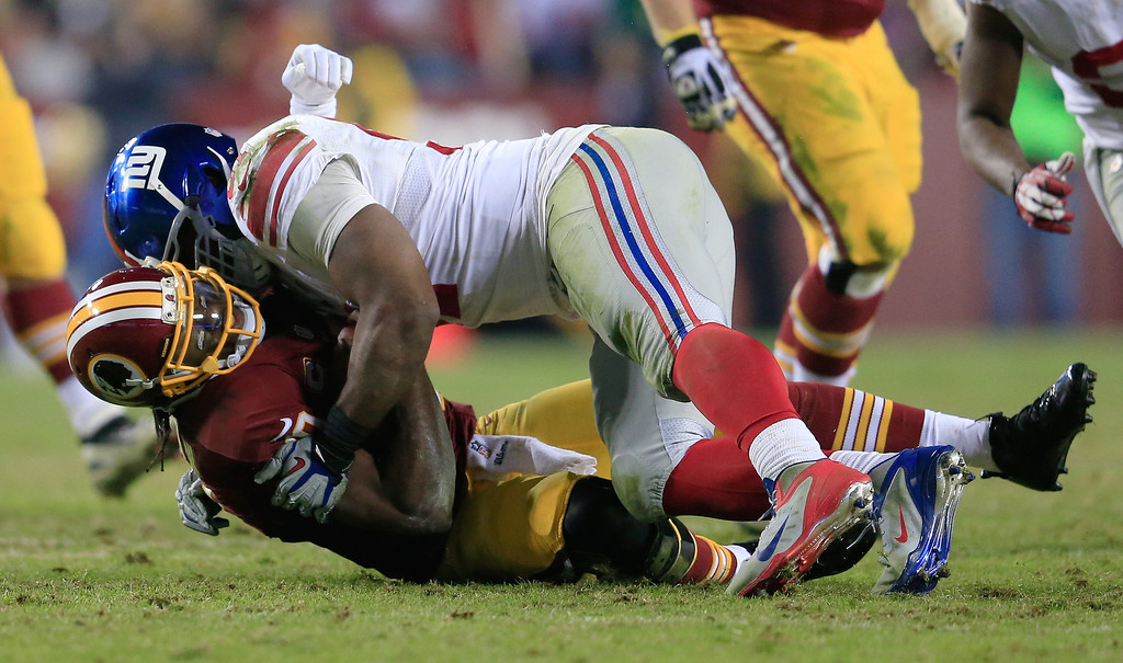 . LANDOVER, MD - DECEMBER 01:  Defensive end Justin Tuck #91 of the New York Giants sacks quarterback Robert Griffin III #10 of the Washington Redskins during the fourth quarter of the Giants 24-17 win at FedExField on December 1, 2013 in Landover, Maryland.  (Photo by Rob Carr/Getty Images)