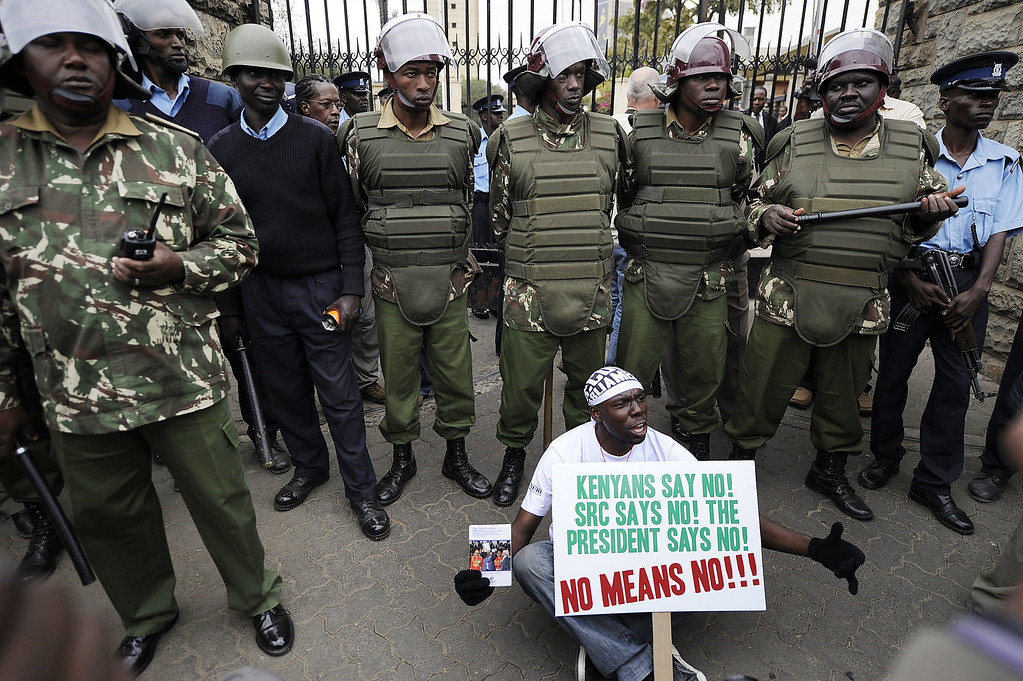 . A protester holds a placard as he sits outside the parliament building main entrance, guarded by police during a demonstration outside the parliament after lawmakers voted themselves hefty salary increases on June 11, 2013 in Nairobi. The protestors had intended to occupy the parliament but were not allowed in by anti-riot police. TONY KARUMBA/AFP/Getty Images
